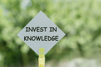 Invest in Knowledge text on paper notes on blur nature background. Business concept.
